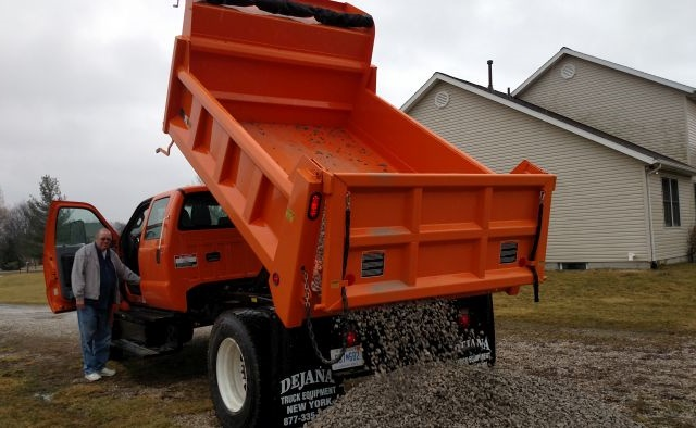 Friend Craig Scott operates push-button controls to finish depositing 2 tons of gravel on his driveway. The electric-over-hydraulic hoist could also tip the body to spread the load.