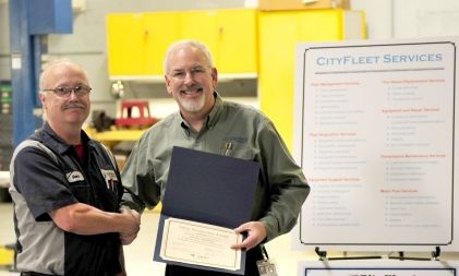 At a fleet meeting, John Hunt, CPFP, the city's fleet manager, awards Dan Adamson, a vehicle and equipment technician, with a Safety Recognition Award. Photo courtesy of the City of Portland.