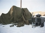 Members of the 354th Logistics Readiness Squadron vehicle maintenance shop work to repair a broken bulldozer in November 2013. They use a portable heater to warm the frozen bulldozer underneath a giant parachute, which traps in heat and helps thaw the vehicle. Jump-starting a frozen battery without first thawing it can cause it to explode, and technicians have to be careful to avoid frostbite while working on vehicles. U.S. Air Force photo by Senior Airman Ashley Nicole Taylor
