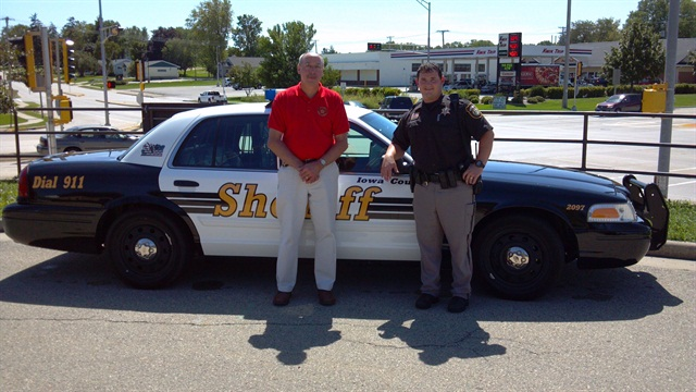 Sheriff Steve Michek said the conversion will save on fuel costs and overall maintenance costs. He is pictured (left) with a deputy.