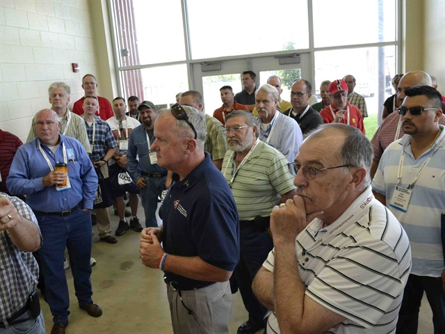 Bob Stanton (in blue) welcomes the first group of tour attendees.
