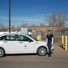 Barbara Connolly, fleet manager and controller for Weld County, stands with one of the County's CNG-fueled vehicles, a Ford Focus, and the County's CNG fueling station.