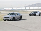 A Dodge Charger Pursuit and Chevrolet Caprice finish their test laps