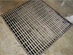 A grate covers a sump in the floor of the car wash that leads to the