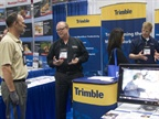 Attendees speak with staff from Trimble.