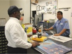 Richard Luna (right), a mechanical stock clerk II, fields requests at