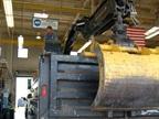 Technician Bob Thyr repairs a dump truck with loader attachment.