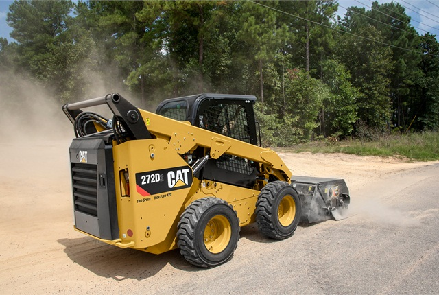 <p>Cat 272D3 SSL with a utility broom in a working application. <em>Photo courtesy of Caterpillar</em></p>